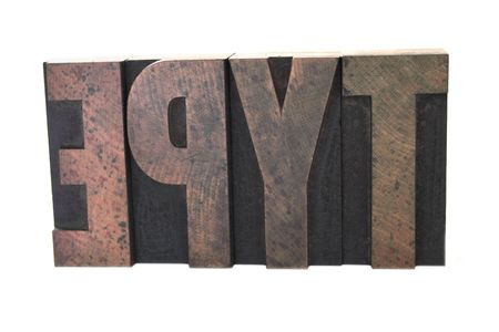 old, inkstained wood letterpress letters form the word 'type' in all caps isolated on white