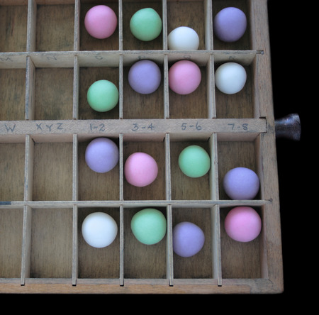 gumballs: a wood type case with pastel gumballs in the slots Stock Photo