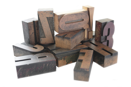 an arrangement of old, inkstained letterpress wood letters isolated on white Banque d'images