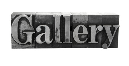 old, ink-stained metal letterpress type spells out the word 'Gallery' isolated on white