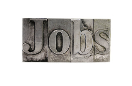 old, ink-stained metal letterpress type spells out the word Jobs isolated on white