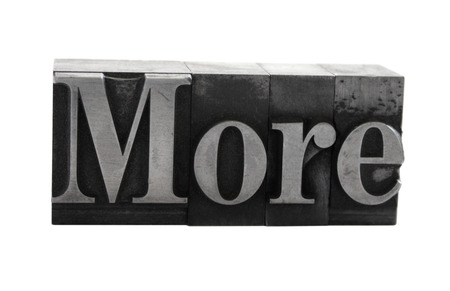 old, ink-stained metal letterpress type spells out the word 'More' isolated on white Stock Photo - 1490377