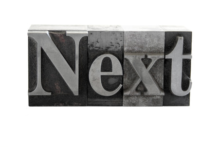 old, ink-stained metal letterpress type spells out the word 'Next' isolated on white Stock Photo - 1490370