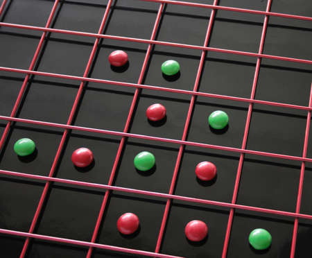 red and green discs within a red grid on top of a reflective black surface