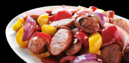 sweet peppers: Polish sausage sauteed with red and yellow bell peppers and red onion on a white platter