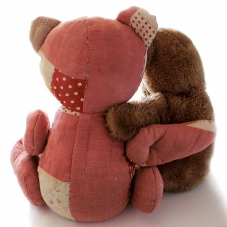 patchwork: a quilted bear and a plush brown bear, each with an arm around the other Stock Photo