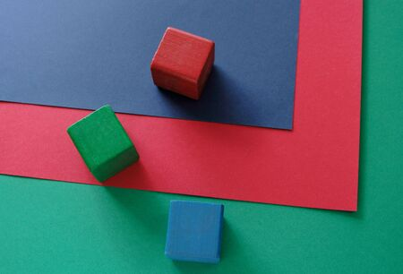 three blocks in red, green and blue on three sheets of red, green and blue paper