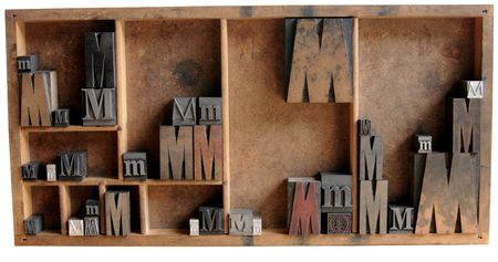 serif: the letter M in upper and lower case and different fonts, both serif and san serif, all in a wood type case