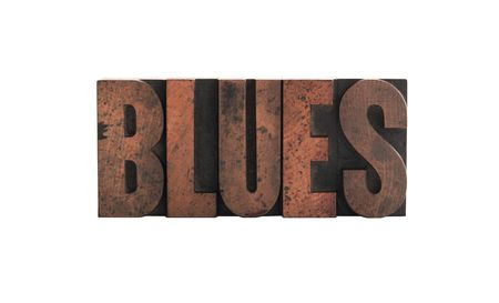 blues: the word blues in old, ink-stained wood letters isolated on white
