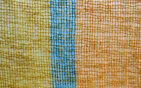 detail of a fuzzy orange, dark yellow and blue knit, suitable for background use