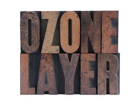 ozone: the phrase ozone layer in ink-stained wood letters isolated on white