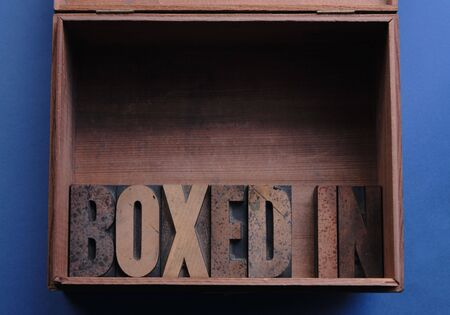 limitations: the phrase boxed in in wood type inside a wood box