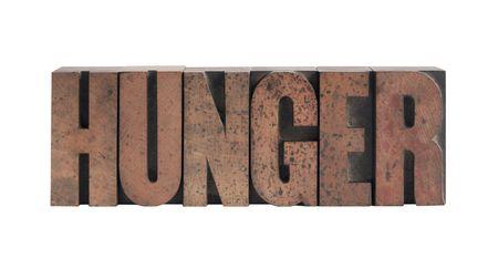 het woord 'honger' in oude, met inkt bevlekte houtsoort Stockfoto