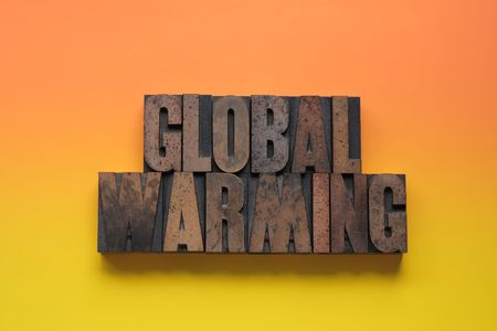 the words global warming against an orange and yellow background