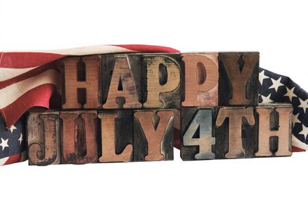 letterpress letters: the phrase happy July 4th in ink-stained letterpress type with flags draped behind Stock Photo
