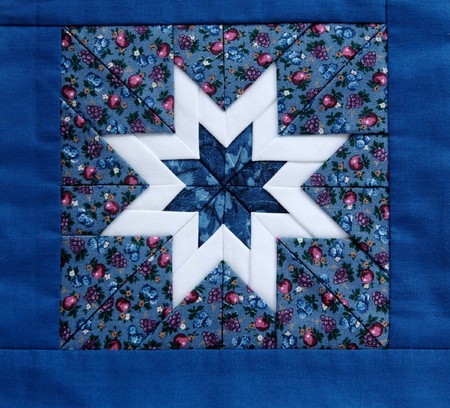 quilted star in white with colorful fabrics and a blue border Banque d'images
