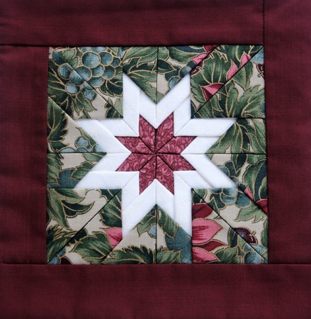 quilted star in white with colorful fabrics and a maroon border