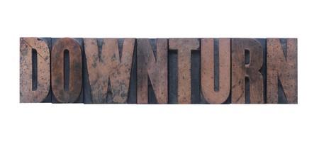 the word downturn in old ink-stained wood type  版權商用圖片