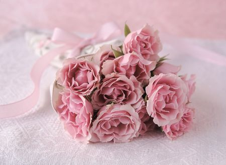 fresh bouquet of miniature roses with a pink ribbon