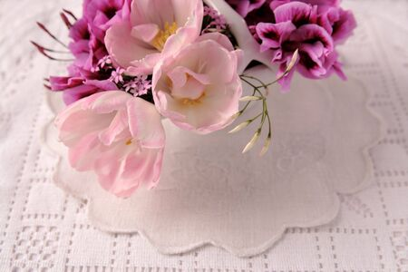 tulips, pelargoniums and breath of heaven flowers on textured linens photo