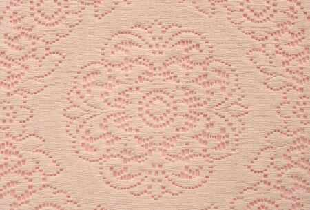 beige lace doily on pink useful for a background