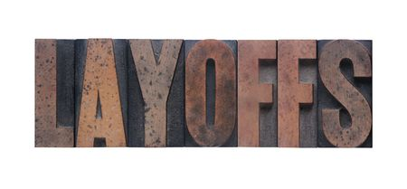 layoffs: the word layoffs in old ink-stained wood type