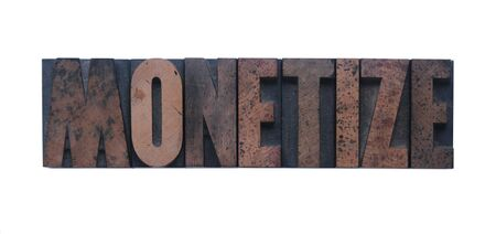 monetize: the word monetize in old ink-stained wood type  Stock Photo