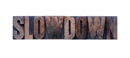 the word slowdown in old ink-stained wood type  版權商用圖片