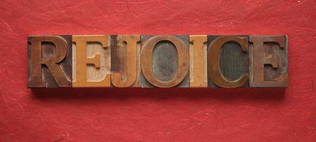 rejoice: the word rejoice in old wood type on a red background