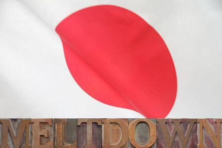 current events: the word meltdown in old wood type on a Japanese flag