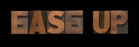 at ease: the words ease up in old wood type Stock Photo