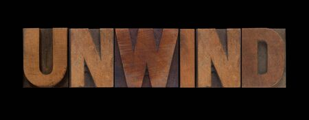 loosen up: the word unwind in old wood type Stock Photo
