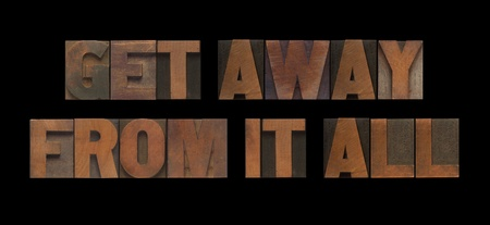 away from it all: the words get away from it all in old wood type Stock Photo
