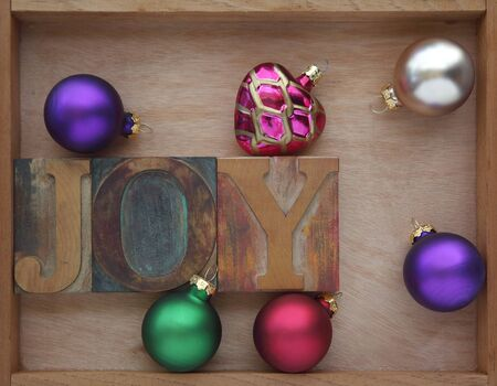 letterpress: the word joy with Christmas ornaments in a wooden box Stock Photo
