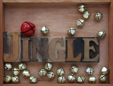 the word jingle surrounded by bells in a wood box Zdjęcie Seryjne