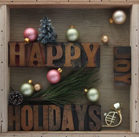 holidays: happy holidays words with ornaments, pine cone, toy horn and Christmas tree