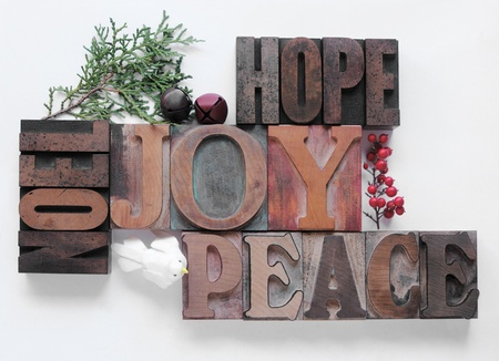 words associated with the Christmas holidays in old wood type with bells, berries, a dove and a sprig of evergreen photo