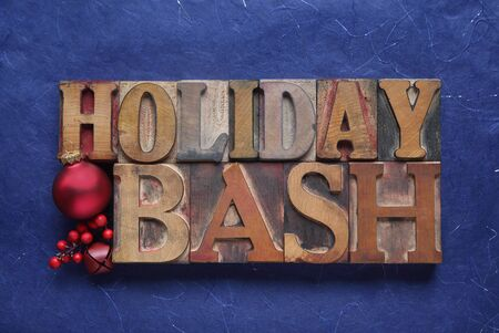 bash: the words holiday bash in old wood type with a red ornament, bell and berries Stock Photo