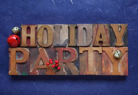the words holiday party in old wood type with red and gold bells and berries photo