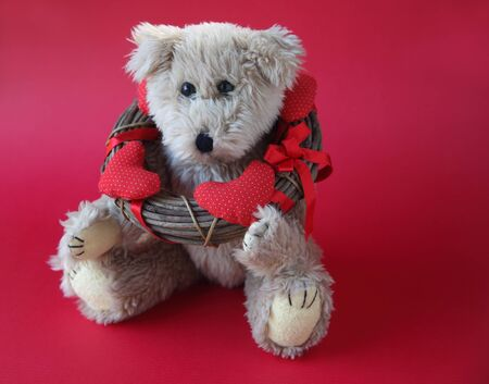 valentine s day teddy bear: generic bear with a wreath of fabric hearts around its neck and copy space