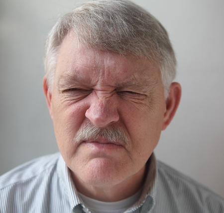 squint: a man wrinkles his nose in disgust