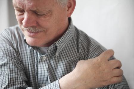senior heer grimassen op de pijn in zijn schouder