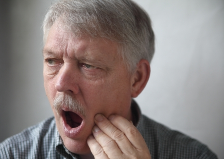 older man showing pain from an aching tooth or jaw