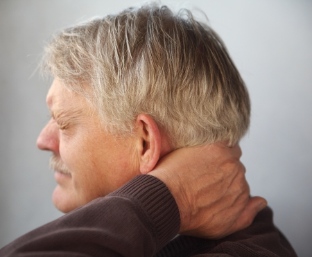 senior man on a neck pain: an older man wincing from pain in the back of his neck