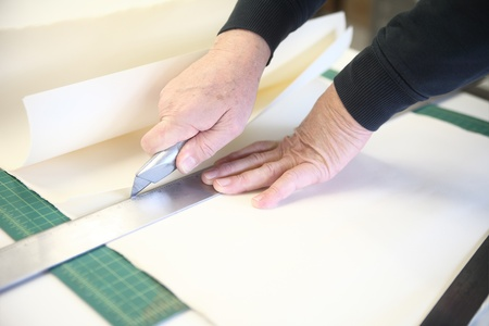 box cutter: an older man cuts paper using a ruler and box cutter