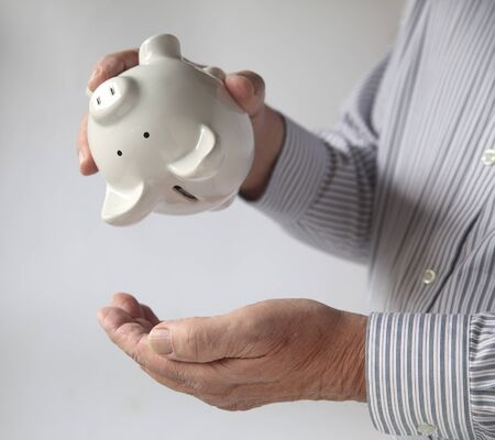 penny pinching: close-up of a man s hands shaking a piggy bank with nothing coming out