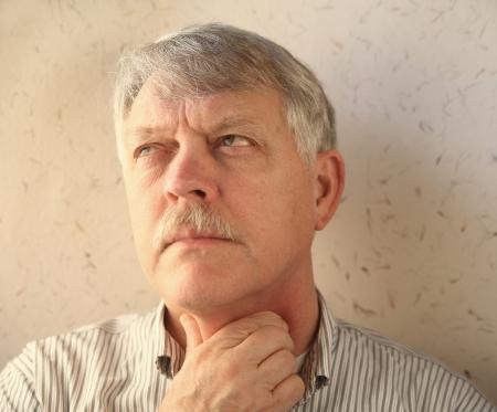 older man rubs his sore throat Banque d'images
