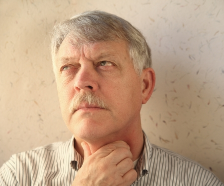 older man rubs his sore throat Stock Photo