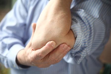 codo: hombre sostiene un codo dolorido Foto de archivo