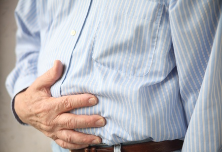 bloating: businessman with stomach pain, hands over abdomen